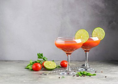 Bloody maria tomato juice smoothie and ingredients tomato, lime, celery, parsley. Strong drinks in two elegant glasses
