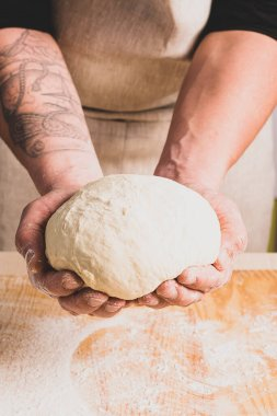 Concept process of making alternative yeast-free home-made bread. A man kneads a kneading pot with dough on the table.