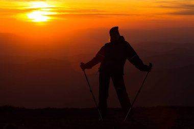Silhouette of a girl on a mountain top on fiery orange background with trekking sticks