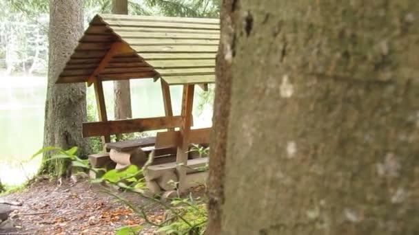 Dřevěný altán pro odpočinek a piknik na břehu jezera lesa