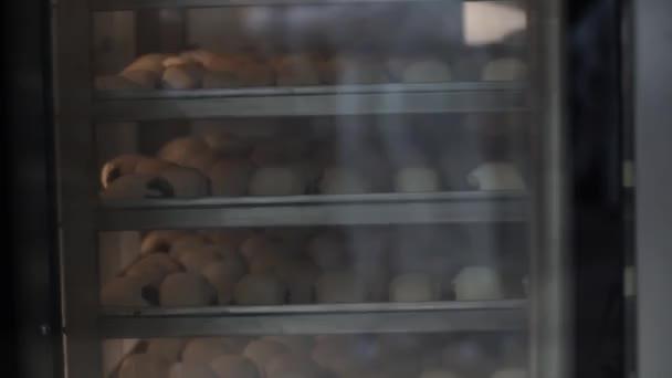 Egy pékség sütőipari termékek gyártása. A Pék rakja a tésztát sütés zsemle.