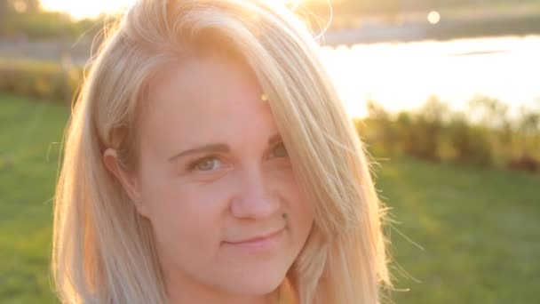 Beautiful face of a blond girl in the evening sun.