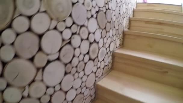Dřevěné schodiště s dekorem dřeva oheň na zdi. Interiér domova s dřevěnou podlahou a schodiště s bílými stěnami