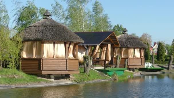 Kyjev, 2. května 2018, Ukrajina: Dřevěné pergoly na břehu jezera. Záclony v altánu rozvíjet ve větru. Došková střecha