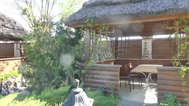 Dřevěné pergoly v zelených rostlinách. Došková střecha