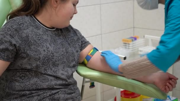 A teenage girl gives blood for analysis. Blood sampling from a vein. Hands in rubber gloves take a blood test from a vein.
