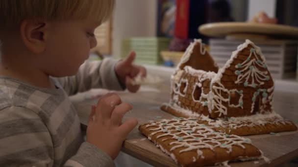 Kinder essen weihnachtliche Lebkuchen. Weihnachten Lebkuchen in Form eines Hauses. Das Kind isst eine Weihnachtskarotte mit Sahne. Sahne für Lebkuchen.