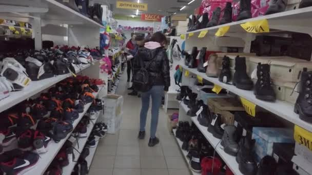 Europe, Kiev, Ukraine - February 2020: The buyer tries on sneakers in a shoe store. Shelves with shoes in a shoe store.