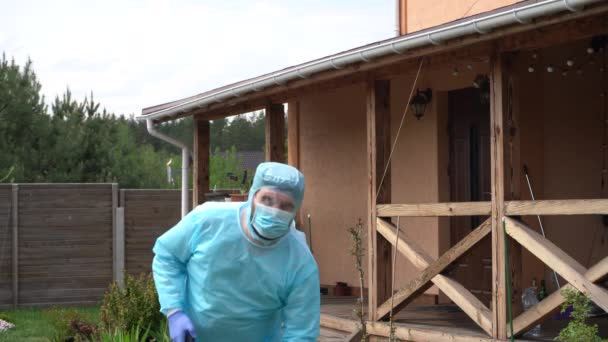 A person in protective shells spray a disinfectant as a precaution against Covid-19 in a private cottage. Epidemic measures. Treatment with an antiseptic solution of coronavirus Covid-19 in a private cottage. Antiseptic cleaning against the virus.