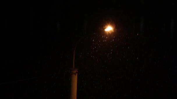Schnee fällt nachts in der Nähe der Laterne