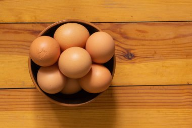 yellow chicken eggs on wooden table table
