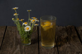 transparent glass with tea and chamomile flowers on a wooden table on gray