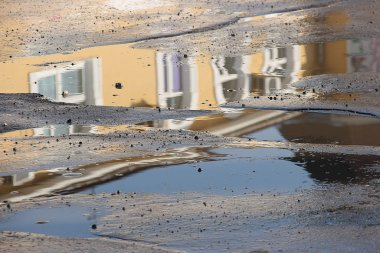 Reflection of a yellow building with white windows in a puddle on the road