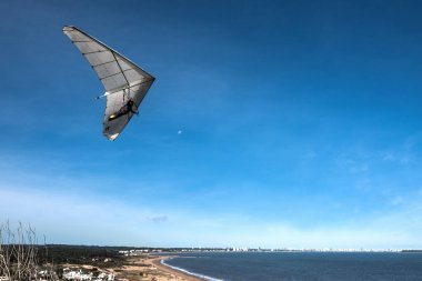 Hang-glider flies over the Punta Ballena cape, Punta del Este
