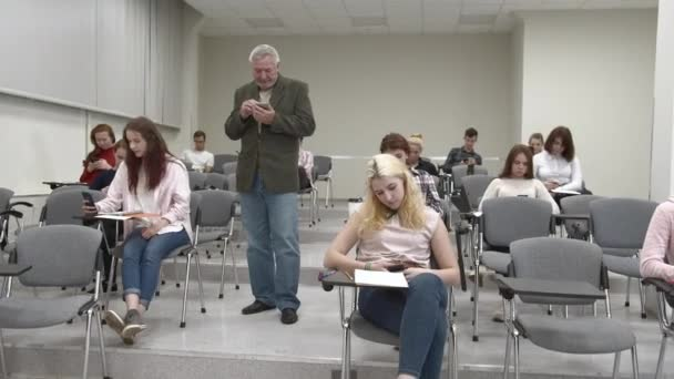 Professor and students look at their phones.