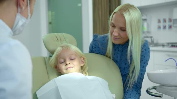 Zubař ukazuje dívce, jak funguje lékařský výcvik