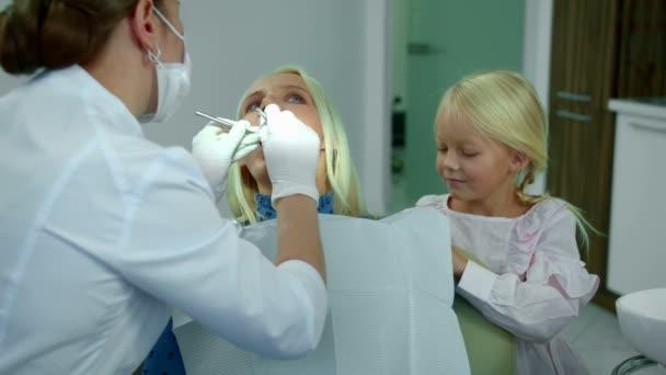 Zubař se dívá na ženské zuby, dcera sedí s ní