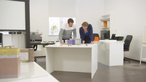 Muž a žena diskutovat o projektu domů v kanceláři