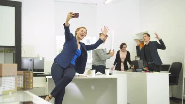 Zpomalený film, žena fotí se svými spolupracovníky během pracovního dne