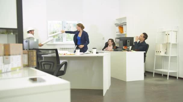 Mann mit Helm und Frau spielen mit Männern, ihre Arbeitskollegen lachen über sie