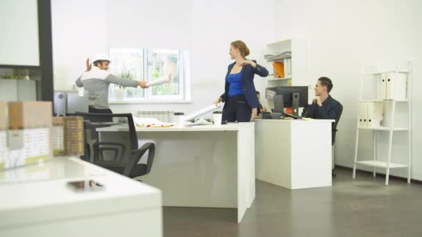 Man in helmet and woman fight with whatmans, their workmates laugh at them