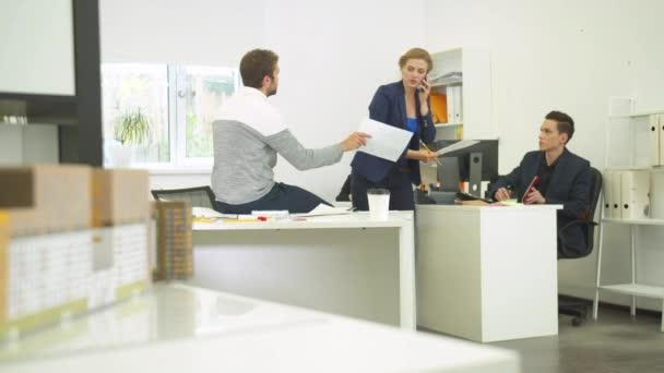 Žena mluvit po telefonu a požádá své kolegy, aby pomohli