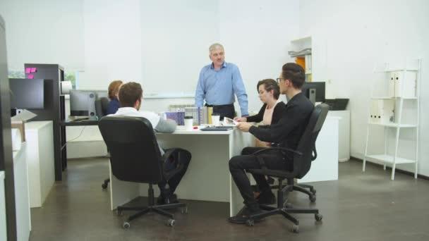 Spolupracovníci sedí u stolu, muž vstát a vysvětlit jim něco