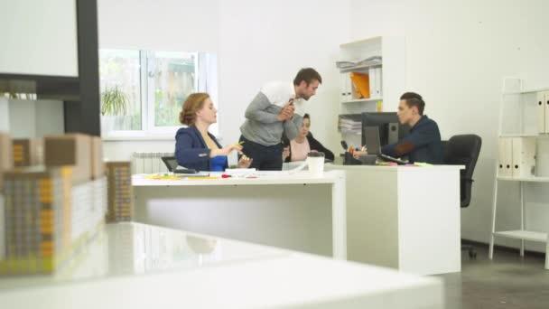 Muž mluví po telefonu a na něco se ptá svých spolupracovníků.