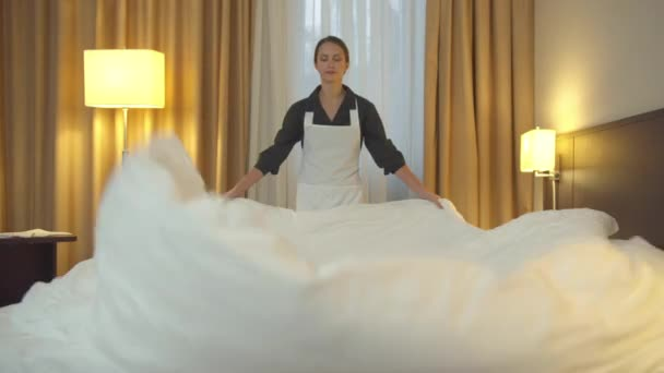 Housemaid in uniform make a bed and spread a blanket in hotel room