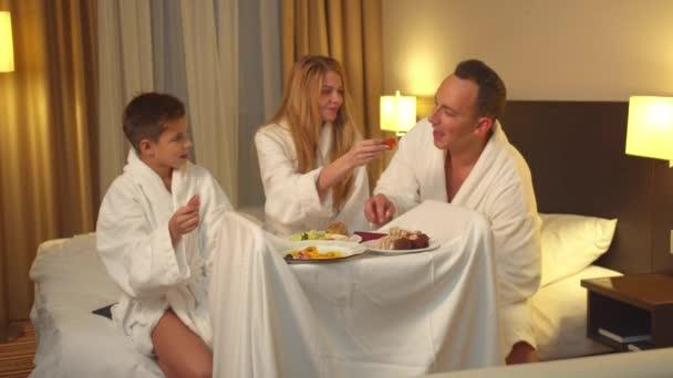 Rodiče a syn sedí na posteli a jedí jídlo v hotelovém pokoji