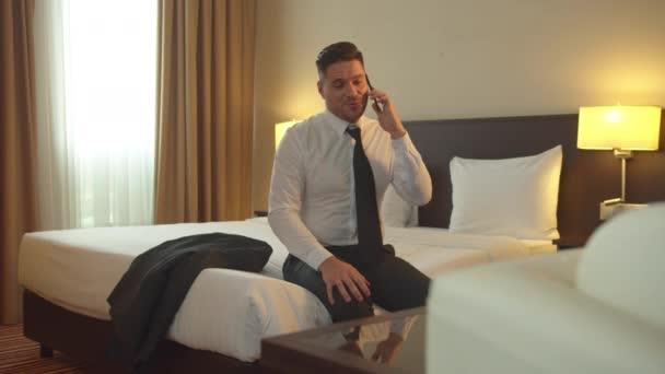 Mann in Hemd und Krawatte sitzt im Hotel auf dem Bett und telefoniert vor Lachen