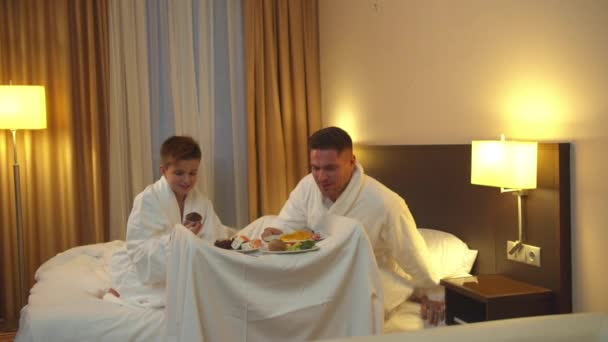 Father and son sit on the bed in hotel room and eat the food
