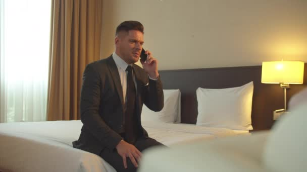Man in suit sit on the bed and talk on phone in the hotel