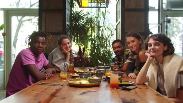 Přátelé sedí v kavárně, dívají se do kamery a usmívají se