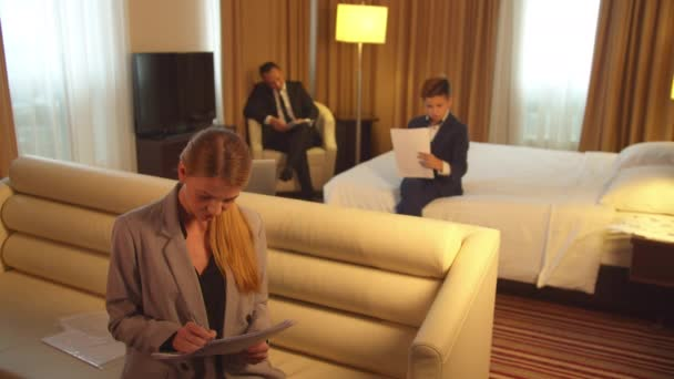 Man, boy and woman in suits sit and work with documents in hotel room