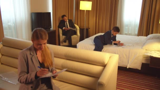 Man, boy and woman in suits work with documents in hotel room