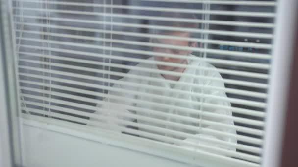 Mann in Schutzkleidung und Brille sitzt im Labor und schreibt etwas