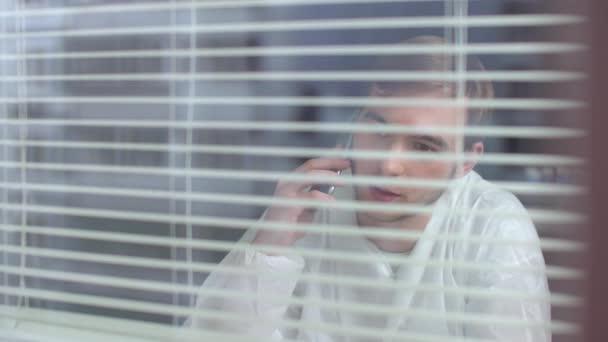 Fiatal férfi védő munkaruhában beszélni telefonon és nevetni a laboratóriumban