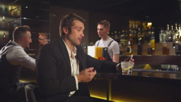 Man sits at the bar and talks by video link on the phone