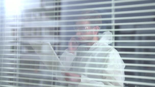 Férfi védő munkaruha és szemüveg beszélni telefonon a laboratóriumban