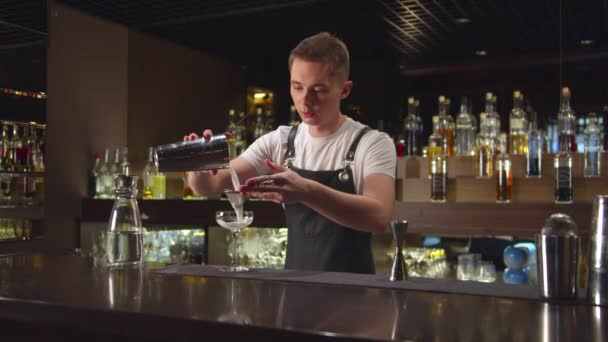 Bartender pours alcohol in glass at the bar