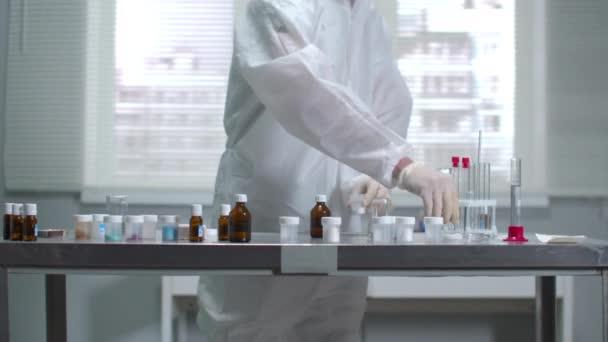 Wissenschaftler in Schutzkleidung und Handschuhen legen etwas Schlauch ins Labor