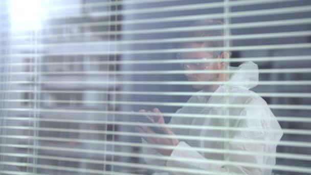 Férfi fehér védő munkaruha és szemüveg áll telefon a laboratóriumban