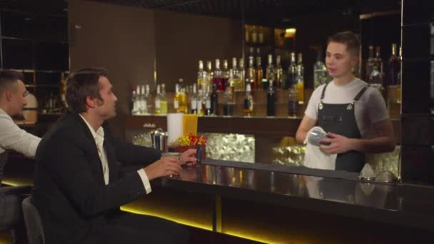 Man sits at the bar, talks to bartender and twirls his credit card