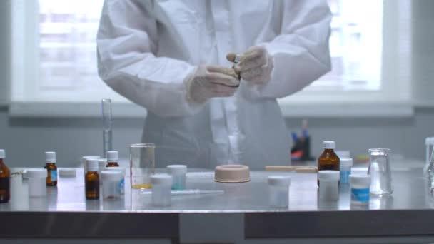 Mann in Schutzkleidung schüttet im Labor etwas auf brennendes Ding