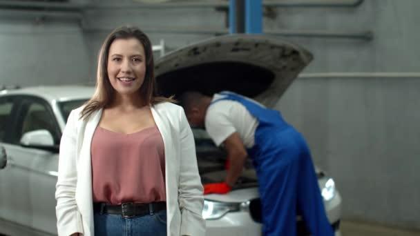 Zeitlupe, Mechaniker repariert Auto, Frau lächelt in die Kamera
