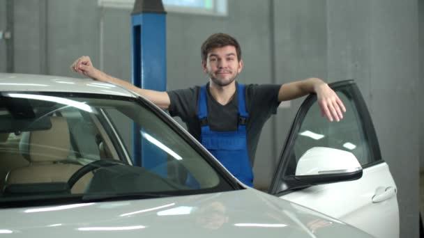 Lassú mozgás, a szerelő egy autó mellett áll és mosolyog.