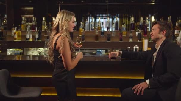 A nő elkezd beszélni egy jóképű férfival a bárban.