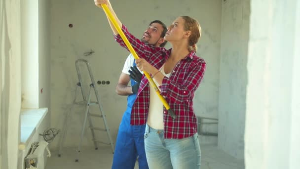 Repairman helps woman to paint a wall, slow motion
