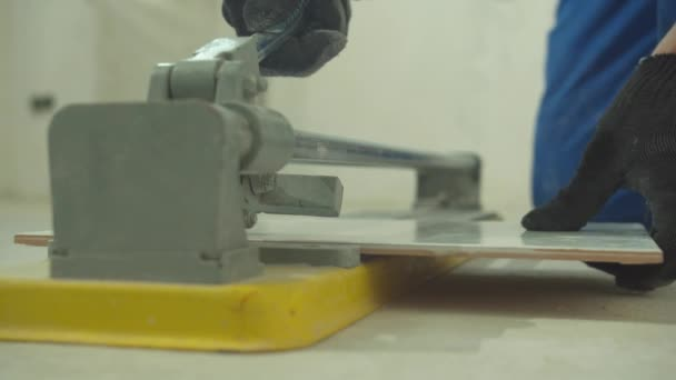 Slow motion, man in protective gloves cuts a tile